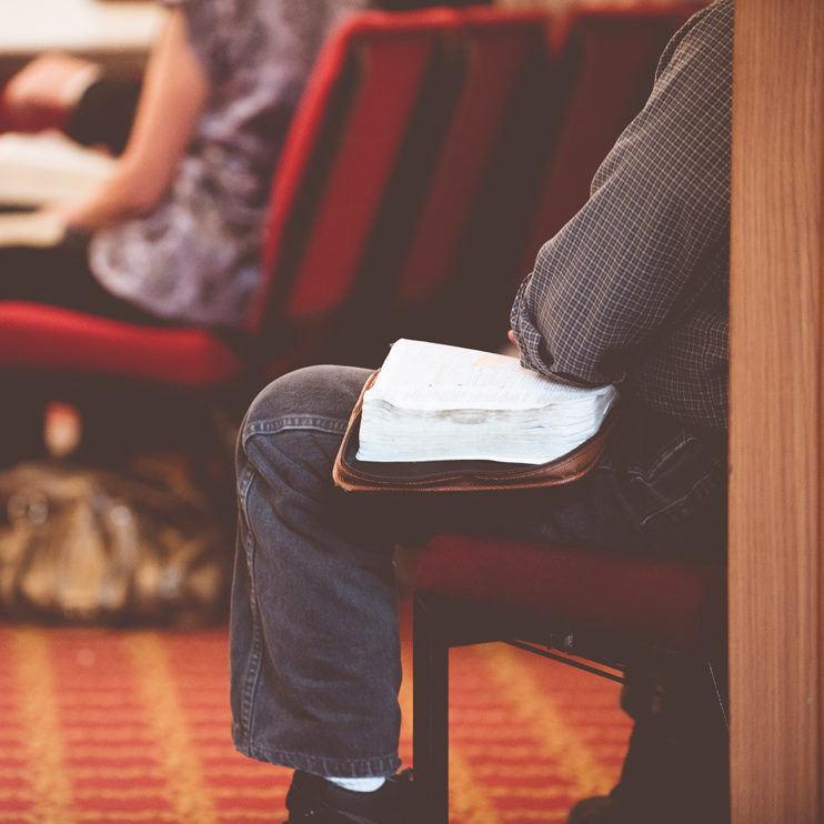 Man sitting in church with his Bible Open